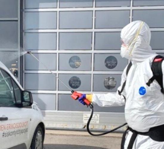 Desinfiointisiivous on käynnissä ja suojavarusteisiin pukeutunut siivoojaa sumuttaa desinfiointiainetta.